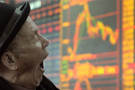 A man yawns in front of an electronic board showing stock information at a brokerage house in Taiyuan, Shanxi province February 9, 2011. REUTERS/Stringer