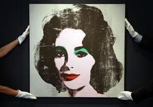 <p>Empleados posan con un retrato de Liz Taylor pintado por Andy Warhol en una subasta de Christie's, en Londres. La estrella del cine Elizabeth Taylor fue admitida en un hospital de Los Angeles para tratar los síntomas de una insuficiencia cardíaca, dijo el viernes su portavoz. REUTERS/Stefan Wermuth (G.BRETAÑA)</p>