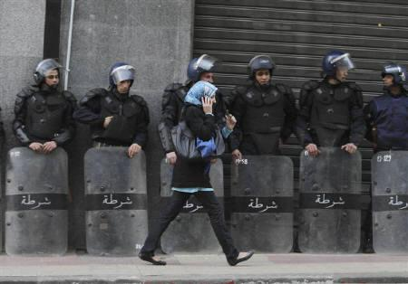 A woman talks on the phone as she walks past riot police standing guard during a demonstration in Algiers February 12, 2011.  REUTERS/Louafi Larbi