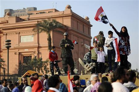 Young anti-government protestors wave flags as they pose for photographs on top of an army vehicle at Tahrir Square in Cairo February 12, 2011. REUTERS/Dylan Martinez