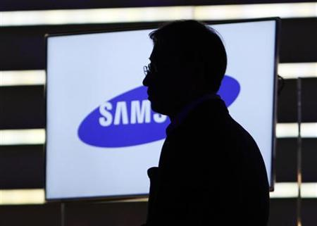 Yoon Boo-keun, head of Samsung's TV division, watches a video at the Samsung keynote address on the opening day of the Consumer Electronics Show (CES) in Las Vegas January 6, 2011. REUTERS/Rick Wilking