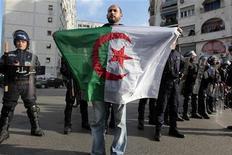 <p>Демонстрант держит флаг Алжира во время протестов в Алжире 12 февраля 2011 года. Власти Алжира пообещали в ближайшие дни отменить введенное 19 лет назад чрезвычайное положение, чего добиваются вдохновленные революциями в Тунисе и Египте сторонники оппозиции. REUTERS/Zohra Bensemra</p>