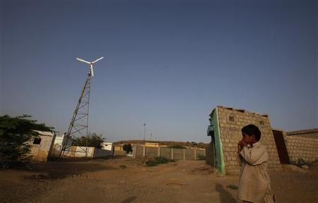 A boy stands near a wind turbine that produces energy in a village at Hub about 25 km (15 miles) northwest of Karachi June 18, 2010. REUTERS/Akhtar Soomro