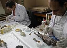 <p>Experts work on restoring damaged artifacts in the Egyptian Museum, located near the opposition stronghold of Tahrir Square, in Cairo February 10, 2011. REUTERS/Steve Crisp</p>