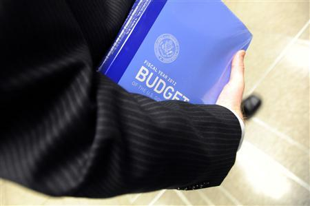 A Senate staffer carries a copy of President Obama's proposed 2012 federal budget on Capitol Hill, February 14, 2011. REUTERS/Jonathan Ernst