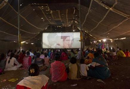 Villagers sit as a movie is projected onto a screen inside a travelling talkie tent in the village of Ond, 300km (186 miles) south of Mumbai, February 9, 2011. REUTERS/Danish Siddiqui