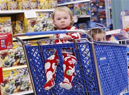 Two children sit inside a shopping cart during Black Friday sales at the Toys R Us store in Carle Place, New York, November 26, 2010. REUTERS/Shannon Stapleton