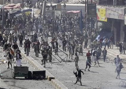 Government backers hurl rocks at anti-government protesters during clashes in Sanaa February 17, 2011. REUTERS/Khaled Abdullah