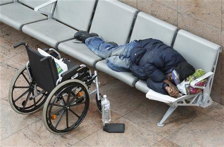 A man sleeps near a wheelchair at the Zaventem international airport near Brussels April 16, 2010. REUTERS/Francois Lenoir