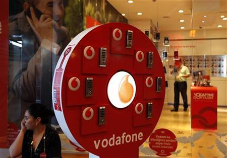 A woman talks on her mobile phone in front of a Vodafone store at Vodafone Turkey headquarters in Istanbul May 4, 2010. REUTERS/Murad Sezer