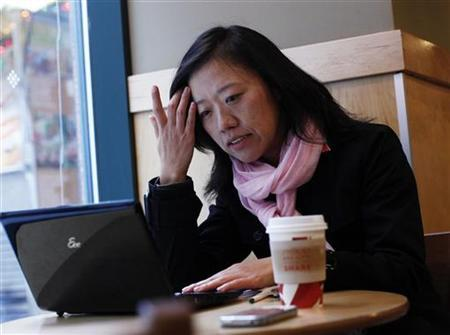 Amateur trader Yan Qin checks her computer for stock reports in New York December 7, 2010. REUTERS/Shannon Stapleton