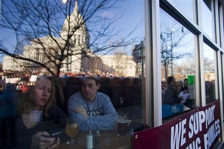 The Wisconsin State Capitol is reflected against a restaurant window together with people gathered to protest against a proposed legislation by Republican Governor Scott Walker to reduce public employee union bargaining power and benefits in Madison, Wisconsin February 19, 2011. REUTERS/Darren Hauck