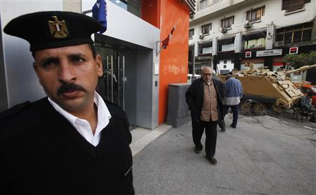 An Egyptian policeman stands guard outside a bank in Cairo February 20, 2011.