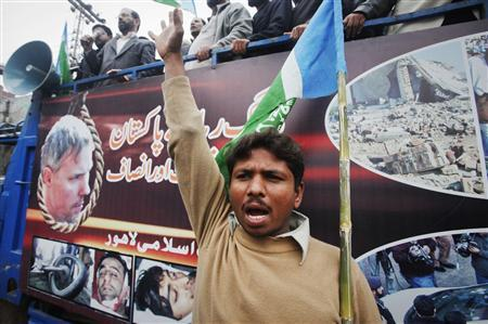 A supporter of the religious and political party Jamaat-e-Islami chants slogans next to an image of American Raymond Davis during a rally in Lahore February 20, 2011. REUTERS/Mohsin Raza