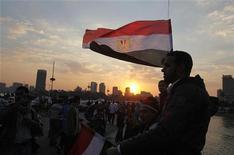 <p>Сторонник оппозиции держит флаг Египта в Каире 12 февраля 2011 года. Несколько оппонентов бывшего президента Египта Хосни Мубарака вошли в кабинет министров в ходе последних перестановок, хотя основные позиции все еще занимают министры сверженного президента. REUTERS/Asmaa Waguih</p>