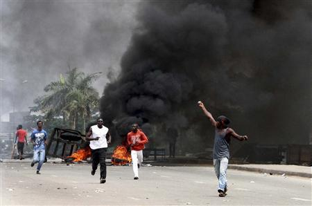 Protesters run past burning tyres at a road block in Abobo, Abidjan February 19, 2011. REUTERS/Luc Gnago
