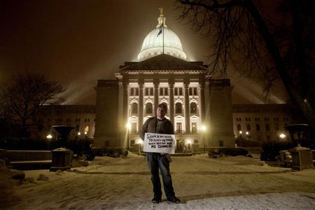 Benjamin Frelka of Madison, Wisconsin poses for a portrait with his sign as he marches around the Capitol while protesters gather to protest against a proposed bill by Governor Scott Walker in Madison, Wisconsin, February 21, 2011. REUTERS/Darren Hauck