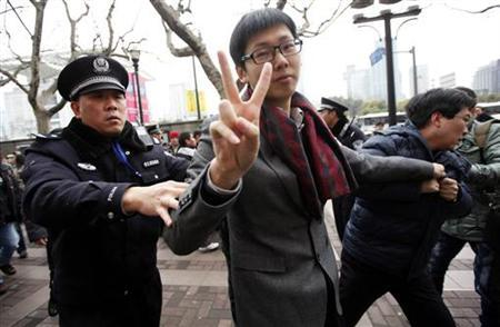 A man arrested by police gestures in front of the Peace Cinema, where internet social networks were calling to join a ''Jasmine Revolution'' protest, in Shanghai, February 20, 2011. REUTERS/Aly Song