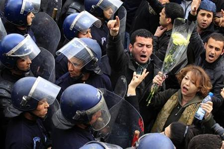 An anti-government protester holding flowers shouts slogans in front of riot policemen during a demonstration in Algier February 19, 2011. REUTERS/Zohra Bensemra