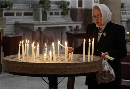 An Orthodox Christian lights a candle at a church in Cairo February 20, 2011. REUTERS/Suhaib Salem