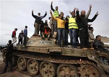 <p>Демонстранты стоят на танке в центре Бенгази 23 февраля 2011 года. Войска, лояльные ливийскому лидеру Муаммару Каддафи, атаковали в четверг антиправительственных демонстрантов в городе Мисрата, убив нескольких человек в ходе битвы за контроль над местным аэропортом. REUTERS/Asmaa Waguih</p>