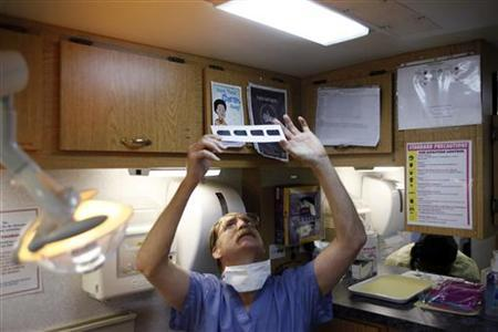 Doctor of Dental Surgery Charles E. Cook looks at x-rays of a patient's teeth inside the Mobile Dental Unit in Houston, Texas, July 28, 2009. REUTERS/Jessica Rinaldi