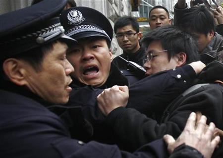 A man is arrested by police after internet social networks called to join a ''Jasmine Revolution'' protest in front of the Peace Cinema in downtown Shanghai, February 20, 2011. REUTERS/Carlos Barria