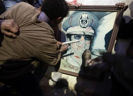 Anti-government demonstrators deface a picture of Libyan leader Muammar Gaddafi in Benghazi February 24, 2011. REUTERS/Asmaa Waguih