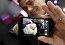 <p>A man displayed the LG Optimus 3D during the GSMA Mobile World Congress in Barcelona February 17, 2011. REUTERS/Gustau Nacarino</p>