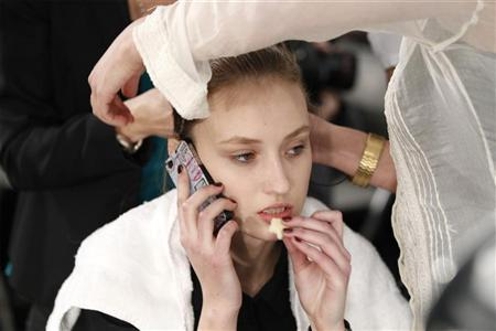 A model eats while using her mobile phone as her hair is styled before the showing of the Cynthia Rowley Fall/Winter 2011 collection during New York Fashion Week February 11, 2011. REUTERS/Lucas Jackson