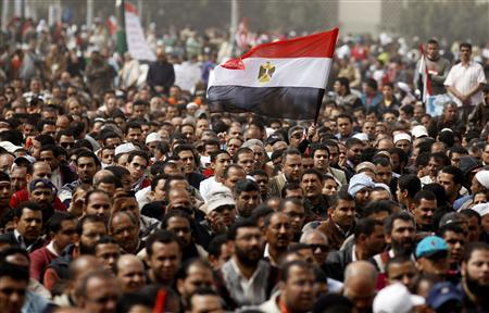 A man holds an Egyptian flag during a rally at Tahrir Square, in Cairo, February 25, 2011. REUTERS/Peter Andrews