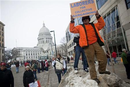 A demonstrator holds a placard near the State Capitol building during protests against the proposed budget cuts from Wisconsin Governor Scott Walker, in Madison February 25, 2011. REUTERS/Darren Hauck
