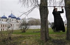 <p>Монах подтягивается около монастыря в Великом Новгороде, 16 апреля 2008 года. Известный православный монастырь близ Калуги решил нести веру в массы, отправляя sms-сообщения россиянам на злободневные темы. REUTERS/Mikhail Mordasov</p>