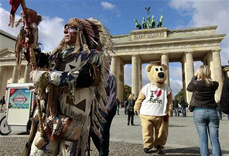 A tourist takes pictures of a man dressed as the Berlin bear as a native American Indian is seen at the Brandenburg Gate in Berlin, September 14, 2010. REUTERS/Fabrizio Bensch (GERMANY - Tags: CITYSCAPE SOCIETY)
