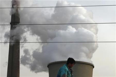 A worker stands atop a petrol tanker in front of a cooling tower emitting steam, from a coal-burning power station in central Beijing February 28, 2011. REUTERS/David Gray