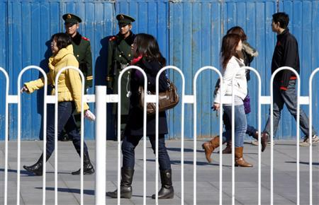 Paramilitary policemen stand guard watching pedestrians walking past near the shopping street of Wangfujing in central Beijing March 1, 2011. REUTERS/David Gray