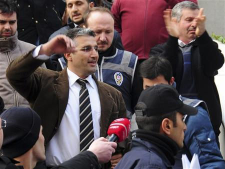Journalist Nedim Sener (L) reacts as he leaves his house escorted by plainclothes policemen in Istanbul March 3, 2011. REUTERS/Stringer
