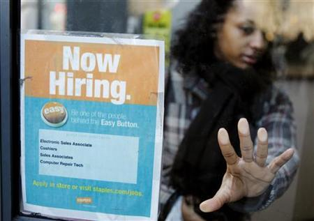 A woman opens a glass door with a ''Now Hiring'' sign on it as she enters a Staples store in New York, March 3, 2011. REUTERS/Lucas Jackson