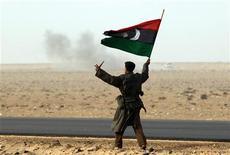 <p>Повстанец держит флаг Соединенного Королевства Ливия и нож в Рас Лануфе 4 марта 2011 года. Сторонники Муаммара Каддафи отбили часть города на западе Ливии, однако повстанцы в ответ смогли захватить нефтеэкспортный порт Рас-Лануф, расширив свое влияние на востоке в ходе затянувшегося на две недели восстания. REUTERS/Goran Tomasevic</p>