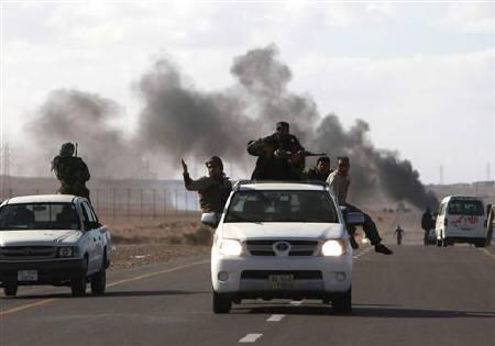 Anti-Gaddafi rebels retreat after a mortar attack by pro-Gaddafi forces close to the area of Bin Jawad March 6, 2011. Libyan troops loyal to Muammar Gaddafi launched counter-offensives against rebel-held towns on Sunday as the popular uprising escalated into open warfare.  REUTERS/Asmaa Waguih
