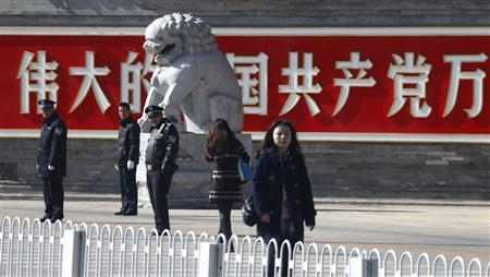 Policemen and security personnel stand guard in front of a sign that reads ''Long live the Communist Party of China'' as members of the public walk past near Tiananmen Square in Beijing March 6, 2011. REUTERS/David Gray