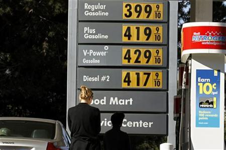 A woman stands in front of gas prices at a petrol kiosk in Dal Mar, California March 1, 2011. REUTERS/Mike Blake