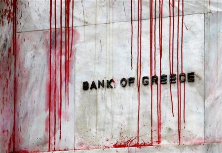 A branch of the Bank of Greece is seen stained with red paint thrown by demonstrators during a protest in central Athens, December 6, 2010. REUTERS/Yannis Behrakis