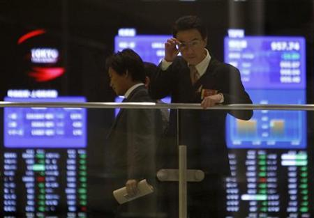 Visitors are seen in front of an electronic board showing stock prices at the Tokyo Stock Exchange in Tokyo February 22, 2011. REUTERS/Kim Kyung-Hoon