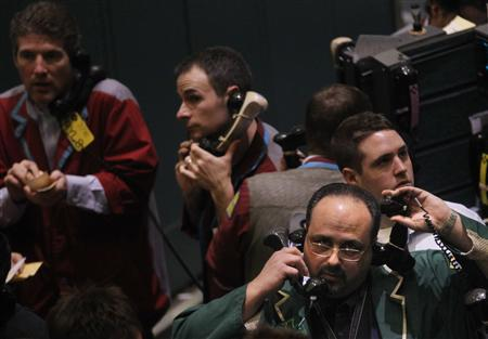 Traders work in the crude oil and natural gas options trading pit on the floor at the New York Mercantile Exchange March 3, 2011. REUTERS/Brendan McDermid