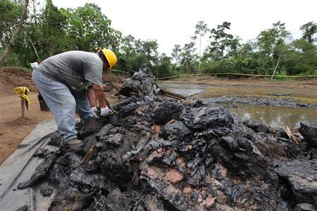 Workers clean up an oil waste pit owned by state petroleum company Petroecuador in Shushufindi, some 410 km (254 mi) east of Quito in this December 8, 2009 file photo. REUTERS/Guillermo Granja