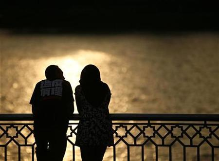 A couple watch a sunset near a lake in Putrajaya December 22, 2008. REUTERS/Bazuki Muhammad