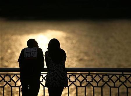A couple watch a sunset near a lake in Putrajaya December 22, 2008. REUTERS/Bazuki Muhammad