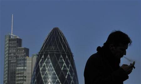 A worker smokes a cigar in the City of London February 9, 2011. REUTERS/Toby Melville