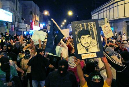 Protesters chant slogans and hold poster of jailed demonstrators during a protest in Qatif March 9, 2011. REUTERS/Stringer